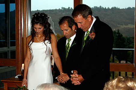Uncle Jack leads the bride and groom in prayer